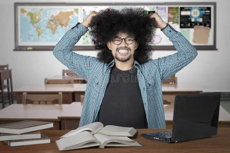 Напряженный студент вытягивая его волосы в классе стоковое фото