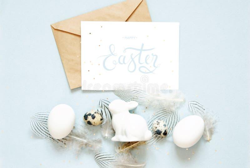 Надпись счастливая пасха, конверт kraft Состав пасхи с пасхальными яйцами, кроликом и пер стоковые изображения rf