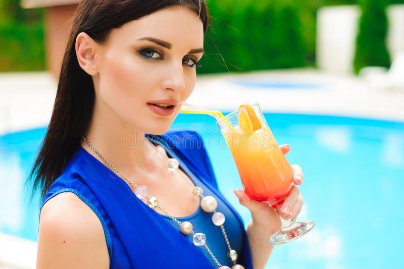 наслаждаться летом Коктейль красивой молодой женщины выпивая пока ослабляющ около бассейна стоковая фотография rf