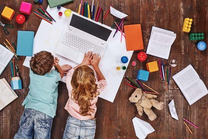 Настолько много вещей Дети лежа около книг и игрушек, пока играющ на компьютере игрушки стоковая фотография