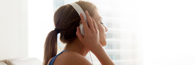 Наушники взгляда со стороны женские нося наслаждаются любимой музыкой дома стоковые фотографии rf