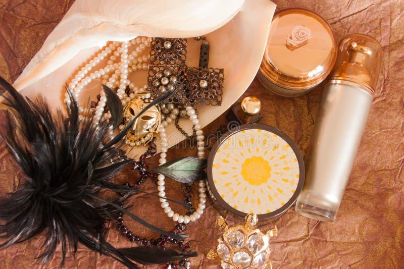 Натюрморт красивых ювелирных изделий в большой раковине, роскошных продуктах заботы кожи и черных пер стоковое изображение