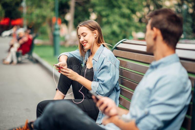 Наркомания, человек и женщина телефона игнорируя один другого стоковые фотографии rf