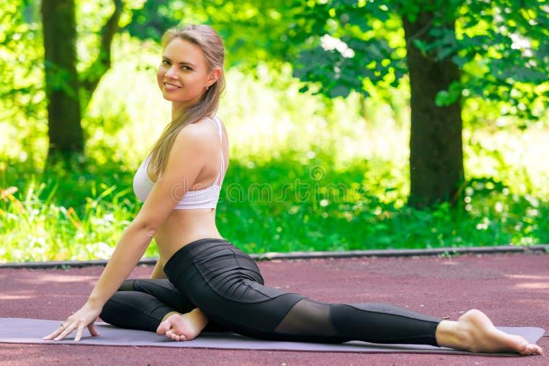 На открытом воздухе йога в парке, портрет красивый водить девушки стоковые изображения