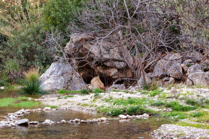 Небольшая пещера в утесах около водопада с зеленым прудом воды Пошлина del Baladre, del Algar Las Fuentes/фонтаны Algar, стоковое фото rf
