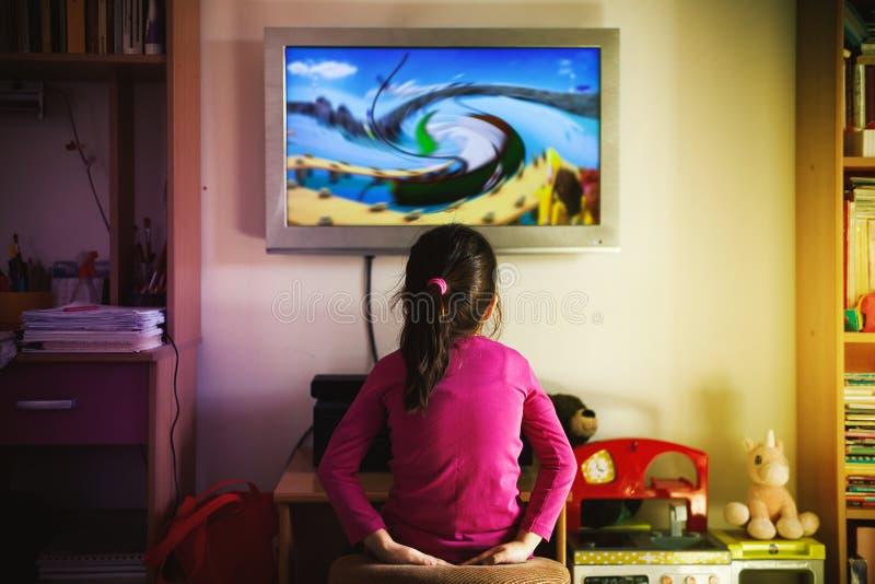 Небольшая девушка наблюдает мультфильм стоковое изображение rf
