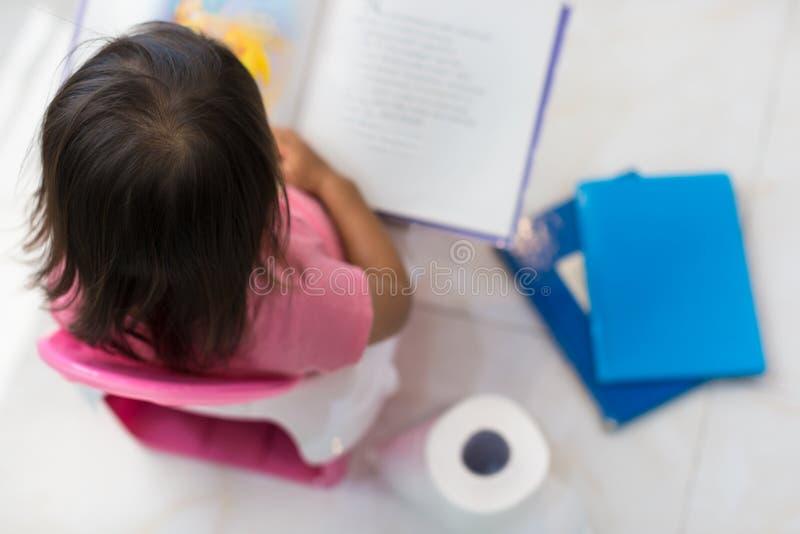 Небольшая тренировка Малыш сидя на туалете читая книгу стоковое фото rf