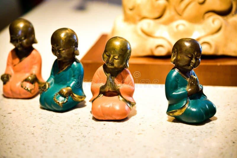 Небольшие красочные статуи маленьких буддийских монахов моля и размышляя стоковые фото