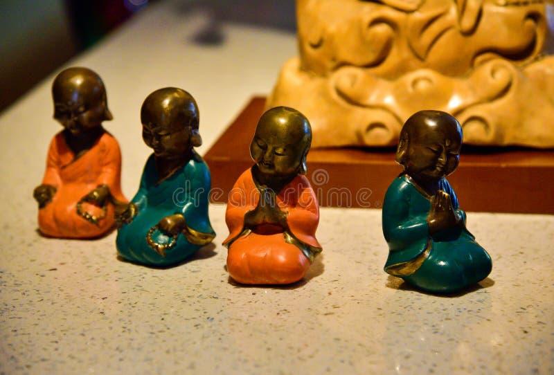 Небольшие красочные статуи маленьких буддийских монахов моля и размышляя стоковые фотографии rf