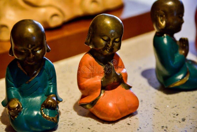 Небольшие красочные статуи маленьких буддийских монахов моля и размышляя стоковые изображения rf