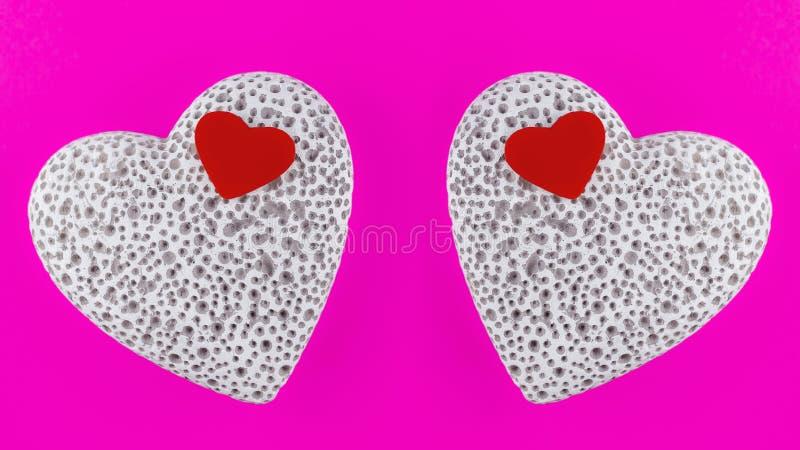 Небольшое красное деревянное сердце лежа на большом белом каменном сердце с порами отражать стоковая фотография rf