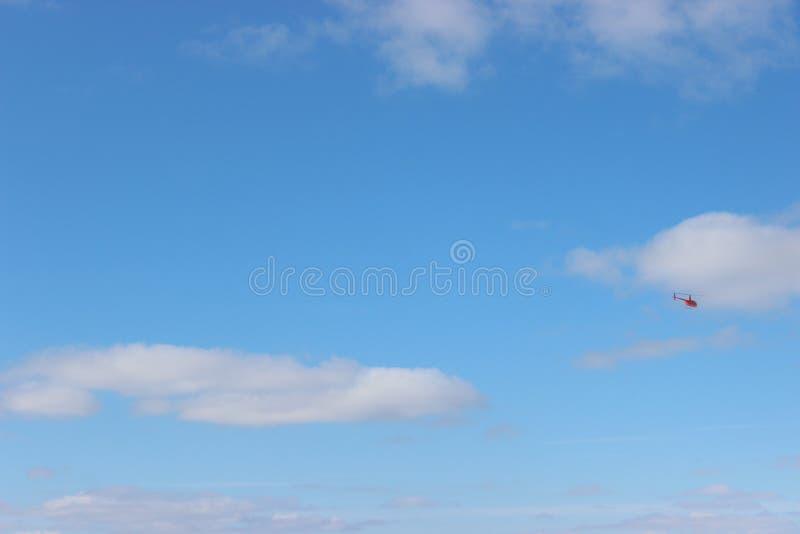 Небольшой вертолет против голубого неба с белыми облаками на солнечный день полет вертолета, эмоции как подарок стоковая фотография