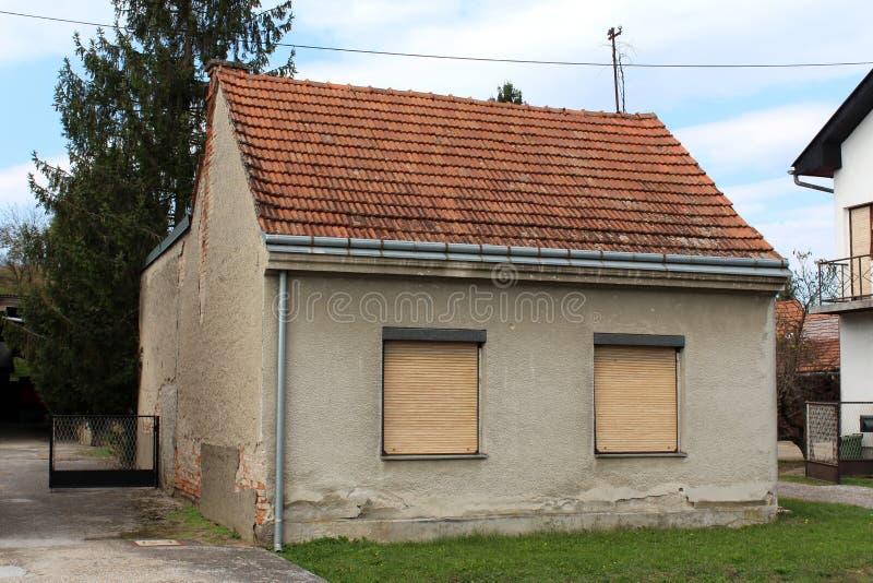 Небольшой получившийся отказ дом семьи с разрушанным фасадом и 2 ветровыми стеклами покрытыми со шторками окна окруженными с трав стоковые изображения