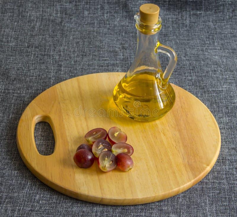 Небольшой стеклянный кувшин с маслом, прерванными виноградинами На деревянной разделочной доске стоковое изображение rf