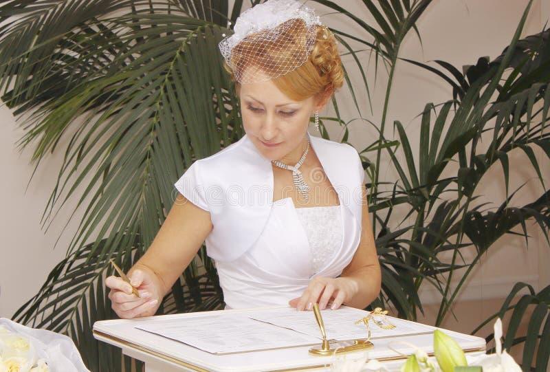 Невеста в платье свадьбы подписывает документы замужества стоковая фотография rf