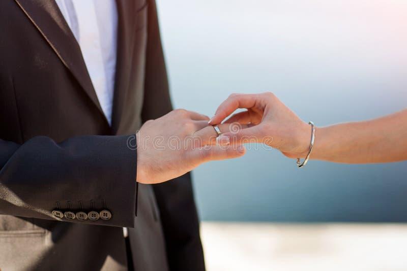 Невеста кладет кольцо на руку холит стоковая фотография