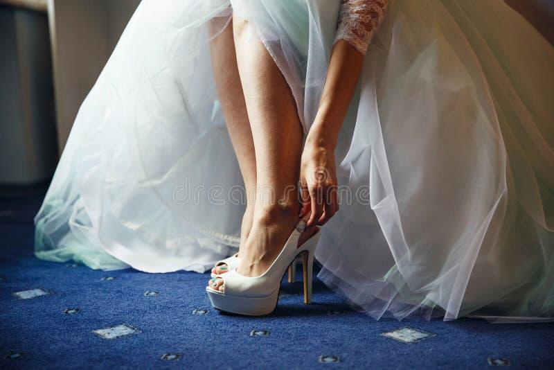 Невеста кладет на белые ботинки в подготовке к свадьбе стоковые изображения rf