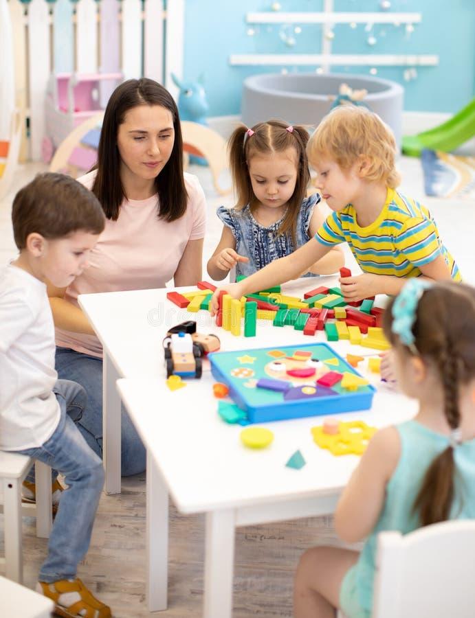 Немногое игра детей с различными игрушками с учителем в daycare Дети строя блоки цвета Воспитательные игрушки для стоковые фото