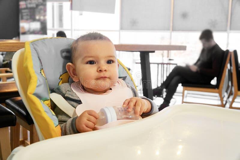Немногое питьевая вода младенца от бутылки внутри помещения стоковая фотография
