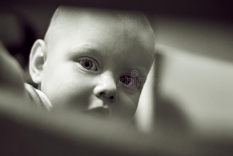 Немногое сиротливый мальчик смотрит из шпаргалки, черно-белого фото стоковое изображение