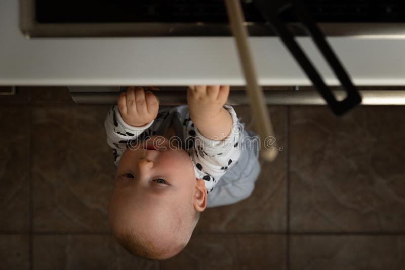 Немногое ребенок играя с электрической плитой в кухне пока сидящ в высоком стульчике Безопасность младенца в кухне стоковые изображения