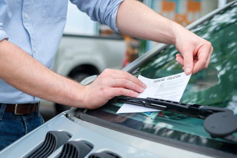 Неправильный штраф штрафа за нарушение правил стоянки помещенный на лобовом стекле автомобиля стоковые изображения rf