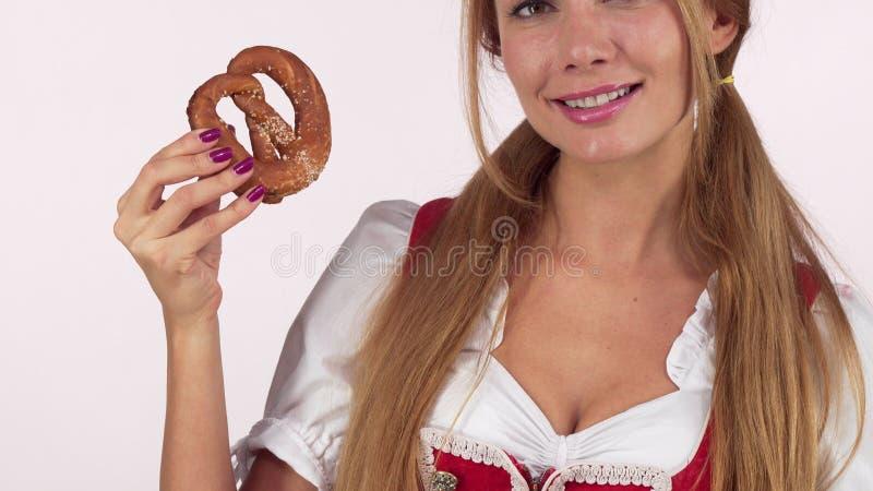 Непознаваемая женщина Oktoberfest лижа губы голодно, держащ очень вкусный крендель стоковые фото