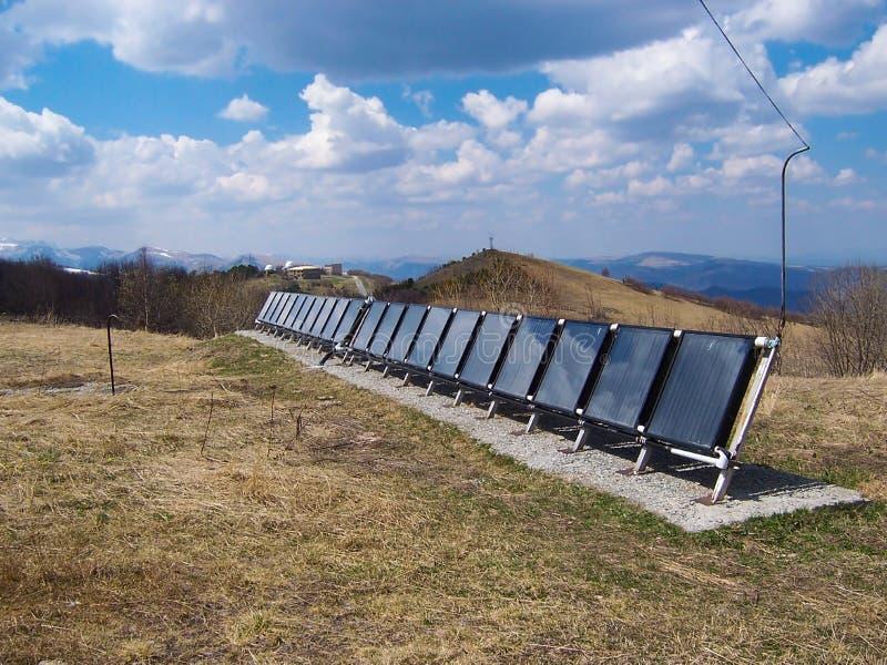 Несколько панелей солнечных батарей обнаружили местонахождение высокую в горах на солнечный весенний день стоковые изображения rf