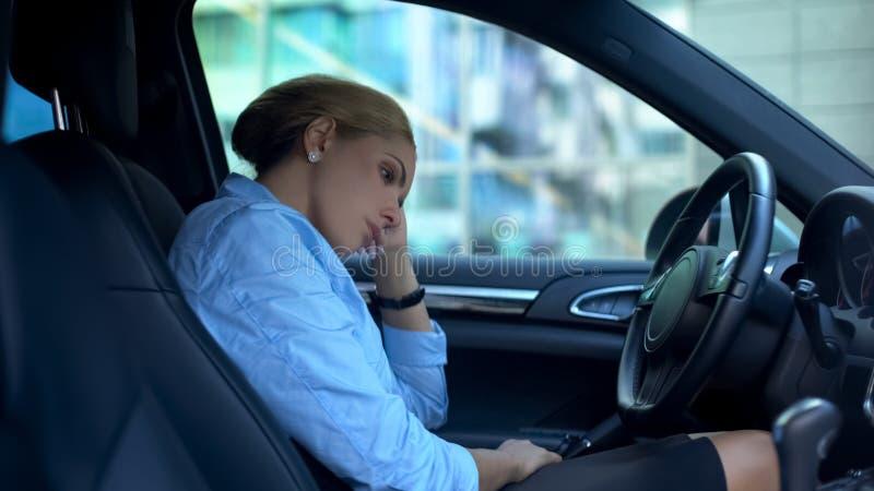 Несчастная женщина сидя в автомобиле, вымотанном после трудного перегружанного рабочего дня, стоковая фотография rf