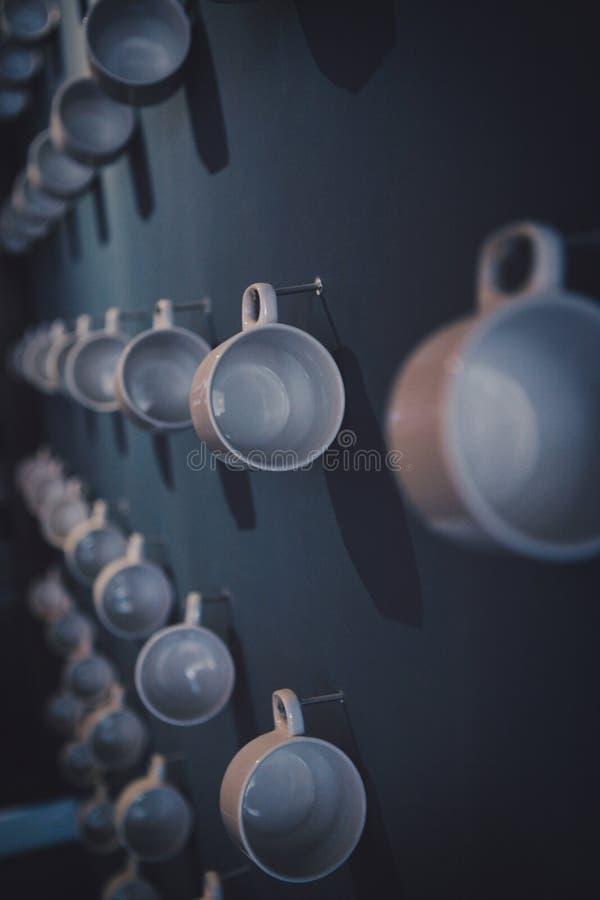 Необыкновенная экспозиция белых чашек чая фарфора вися на стене ручкой стоковое фото