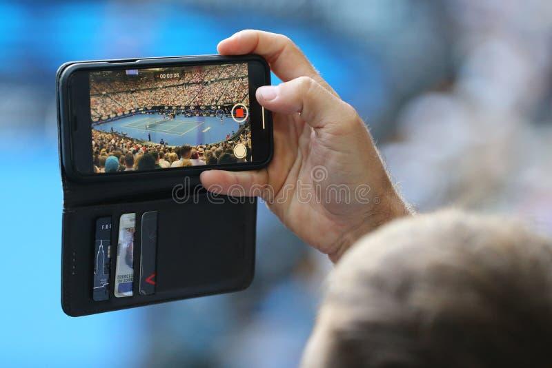 Неопознанный зритель использует его сотовый телефон для того чтобы принять изображения во время спички тенниса на открытом чемпио стоковое изображение rf