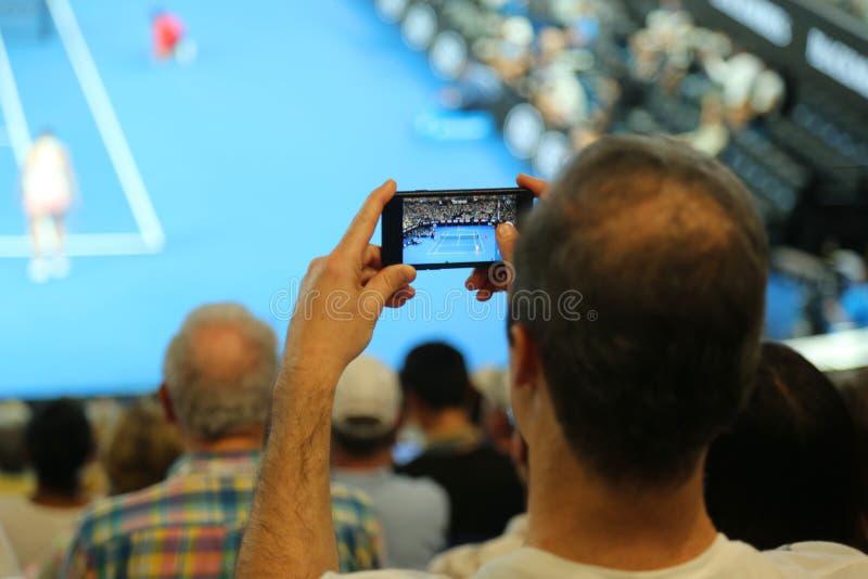 Неопознанный зритель использует его сотовый телефон для того чтобы принять изображения во время спички тенниса на открытом чемпио стоковое фото