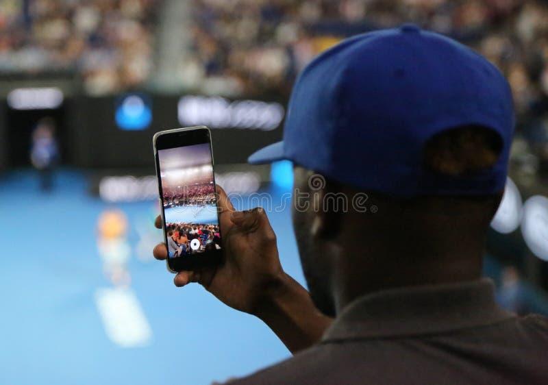 Неопознанный зритель использует его сотовый телефон для того чтобы принять изображения во время спички тенниса на открытом чемпио стоковая фотография