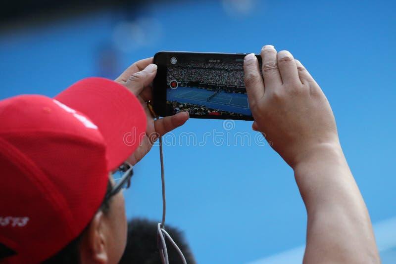 Неопознанный зритель использует его сотовый телефон для того чтобы принять изображения во время спички тенниса на открытом чемпио стоковое фото rf
