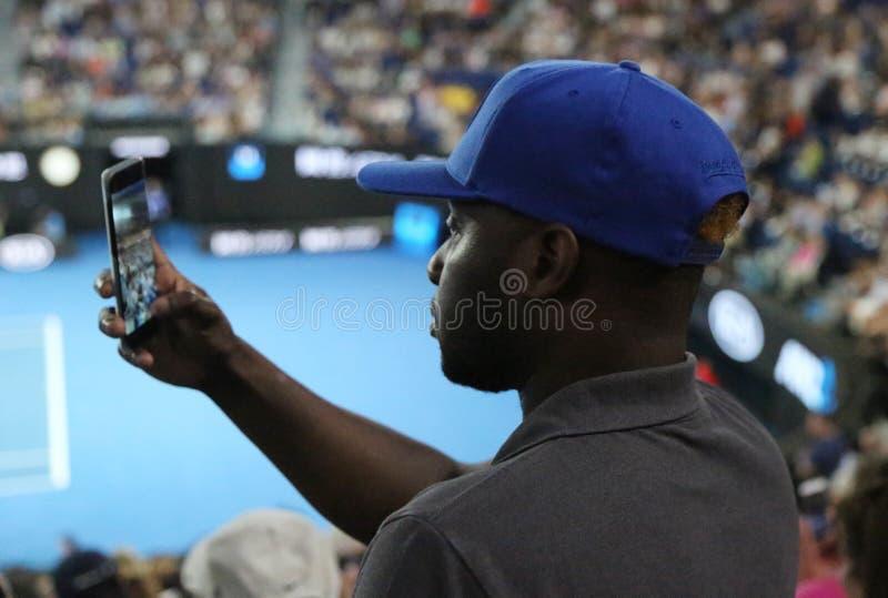 Неопознанный зритель использует его сотовый телефон для того чтобы принять изображения во время спички тенниса на открытом чемпио стоковые изображения rf