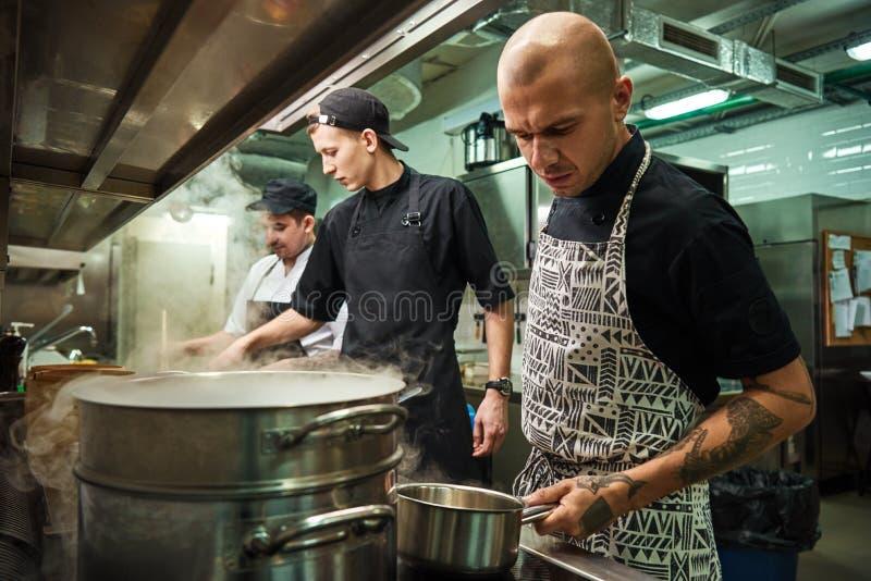 Нужны больше специй Серьезный профессиональный шеф-повар с несколькими татуировок на его удерживании оружий лоток металла пока ва стоковые фотографии rf