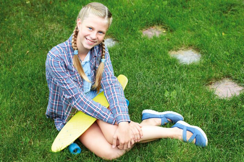 Нappy, laughing child wearing cool fashion clothing posing with colorful skateboard against green grass, urban style royalty free stock image