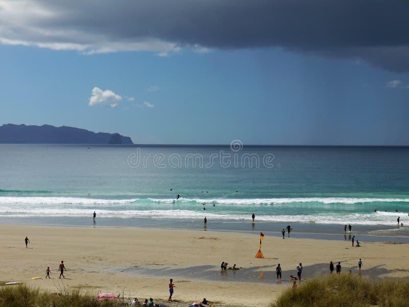 Новая Зеландия: Серферы Mangawhai приставают шторм к берегу дождя стоковое фото rf
