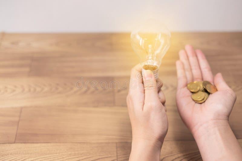 Новая концепция идеи, молодые женщины вручает электрическую лампочку удерживания и монетки на деревянных предпосылках и новой сил стоковая фотография rf
