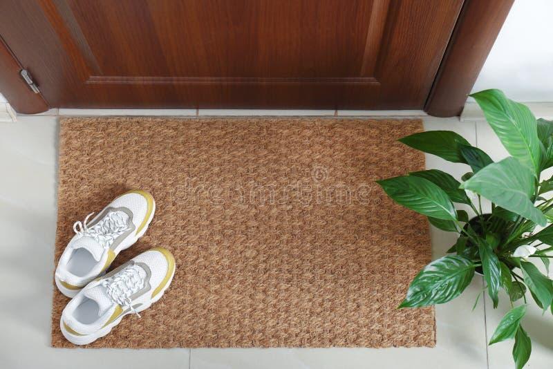 Новая чистая циновка с ботинками около входной двери и комнатного растения стоковые изображения rf