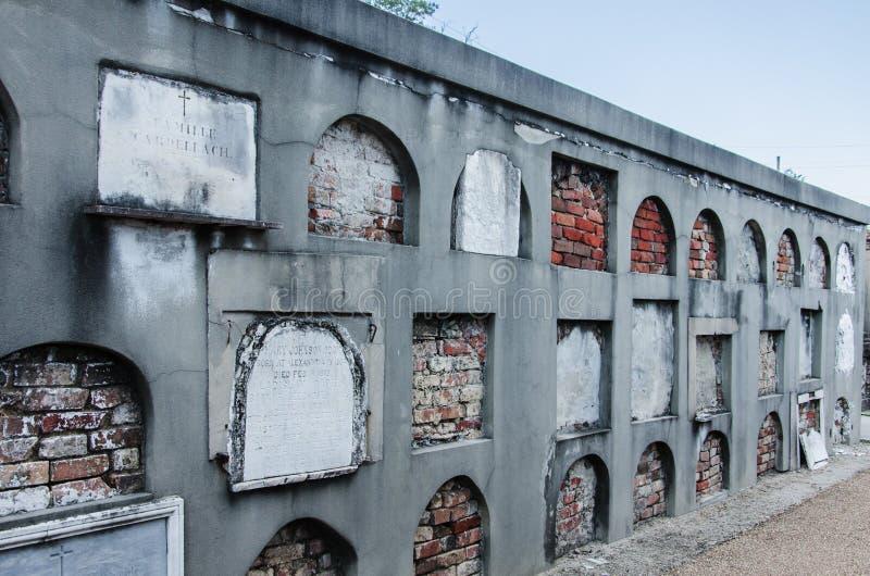 Новый Орлеан, старое кладбище, стена ниш, закладыванных кирпичами усыпальниц, некоторых с металлическими пластинками стоковые фото