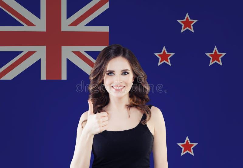 новое перемещение zealand Счастливый студент девушки с большим пальцем руки показа флага Новой Зеландии вверх стоковые изображения rf