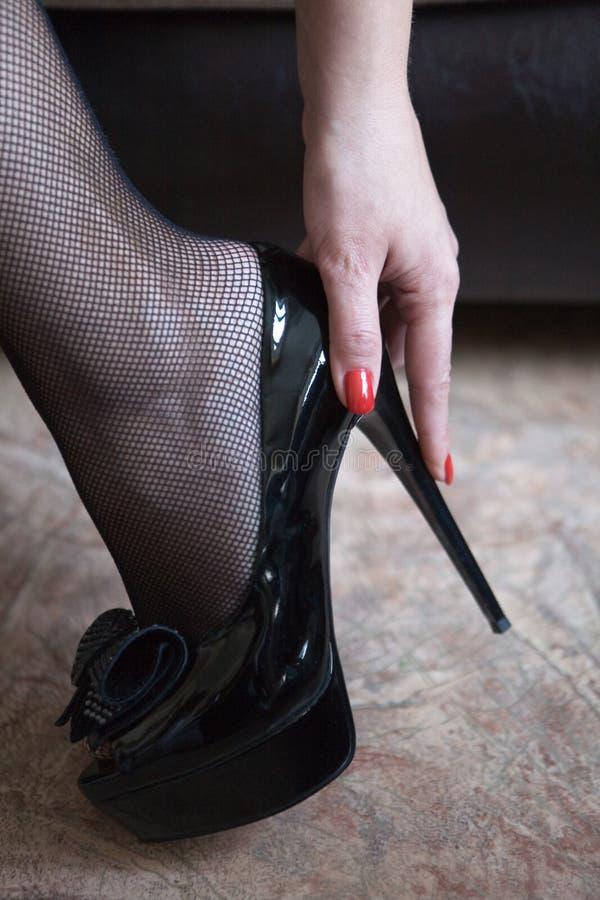 Нога женщин в высоко-накрененном ботинке и ее руке стоковые изображения rf
