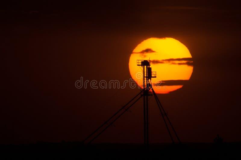 Нога лифта зерна Silhouetted против заходящего солнца стоковая фотография