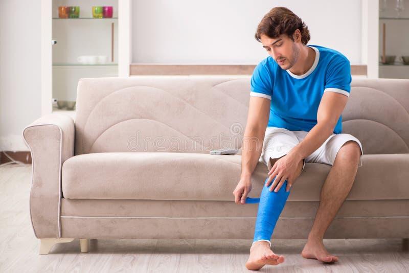 Нога повредила молодого человека на софе стоковые фото
