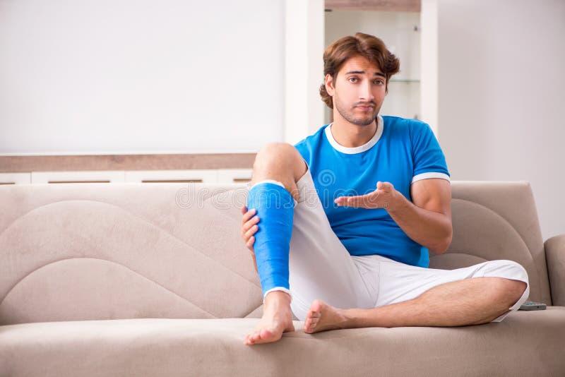 Нога повредила молодого человека на софе стоковые изображения rf
