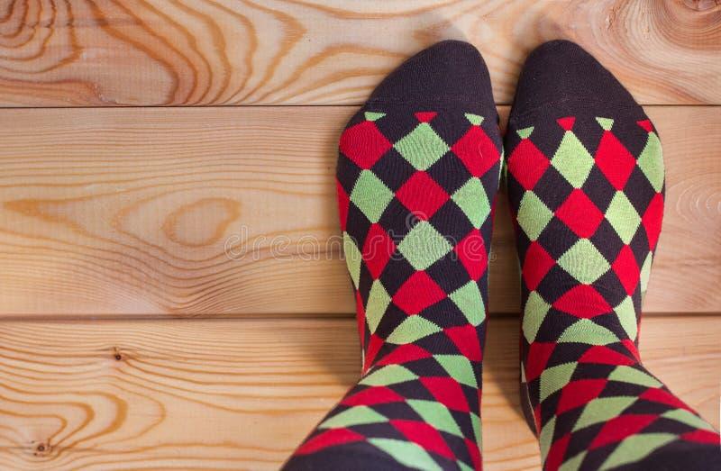 2 ноги в пестротканых носках на деревянном поле стоковые фотографии rf