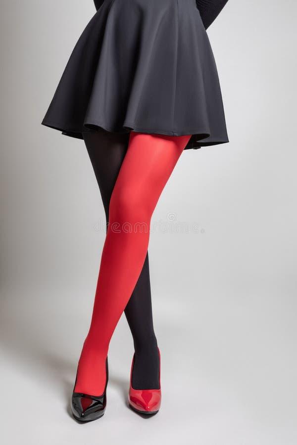 Ноги женщины нося 2 колготки цветаÂ и ботинки других цветов стоковая фотография