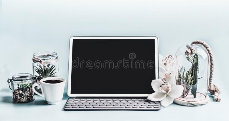 Ноутбук пустого экрана современный с суккулентными заводами в стеклах и цветках орхидеи на таблице Домашний женский офис стоковая фотография
