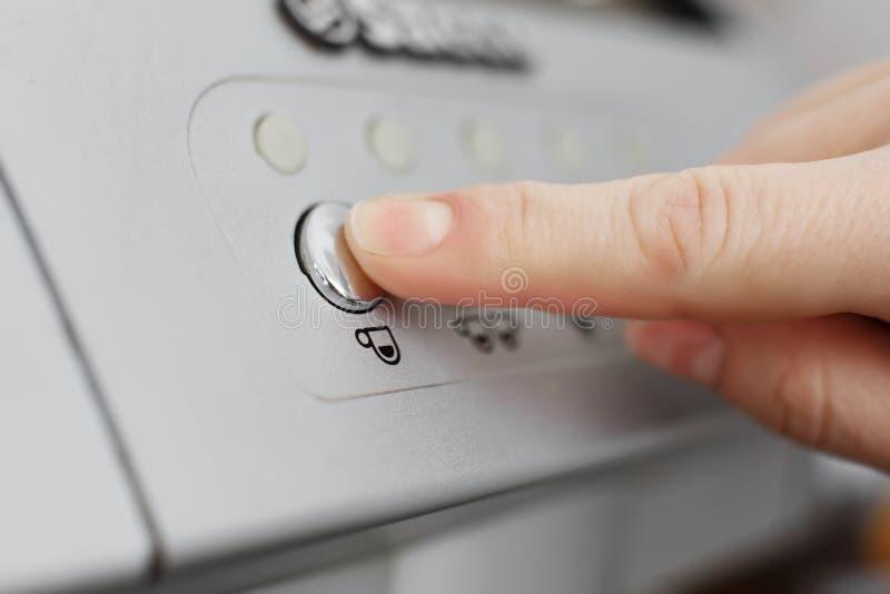 Палец отжимает круглую кнопку под которой чашка кофе нарисована Нажмите для того чтобы сделать кофе стоковое изображение